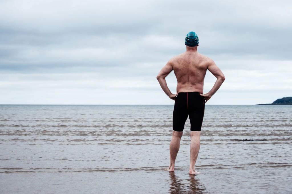 Man standing on sea shore ready to swim