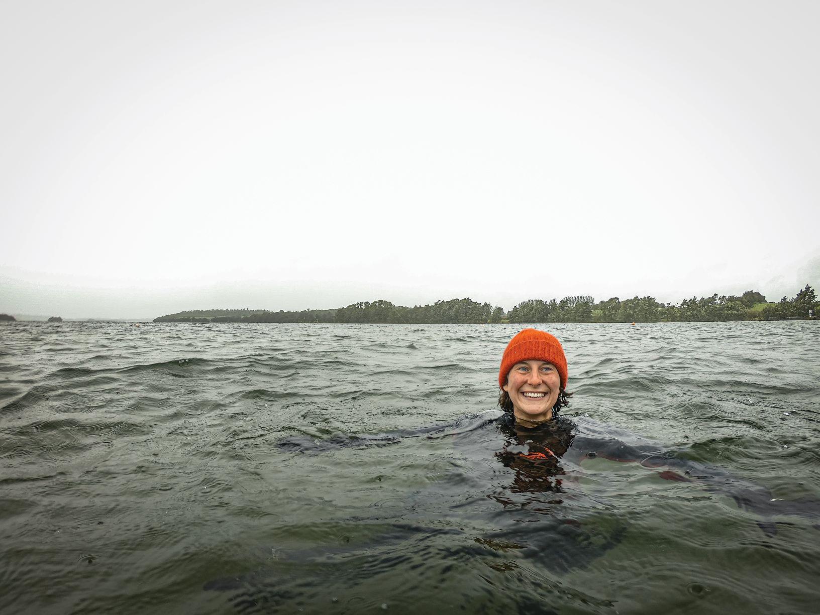Kerri ni Dochartaigh floating in the rainy sea with an orange woolly hat on